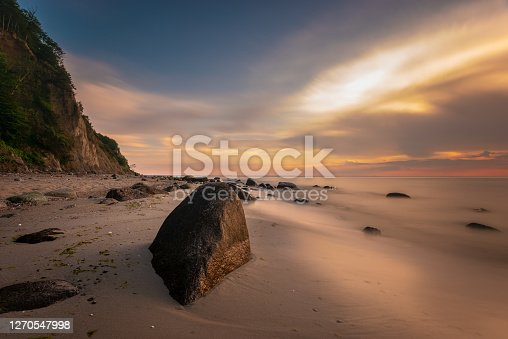 Cliff and stony beach in Wolin National Park in the light of the setting sun, Poland
