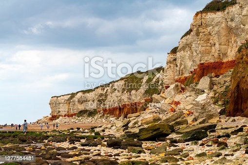 Hunstanton, Norfolk, East Anglia, England, UK. The chalk and sandstone cliffs are constantly being eroded and collapsing on to the beach.  This shows the different coloured rock strata and a pile of collapsed rocks on the beach. There are crowds of people on the beach and some perilously close to the unstable cliffs.