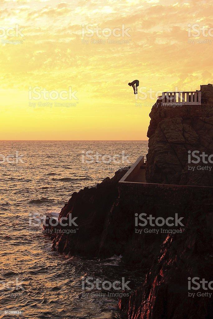 Cliff diver off the coast of Mazatlan at sunset stock photo