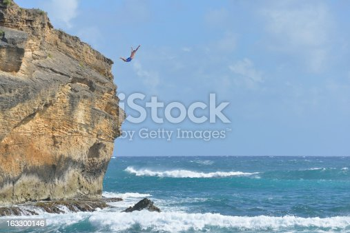 A young man in his 20s is cliff diving in Kauai.