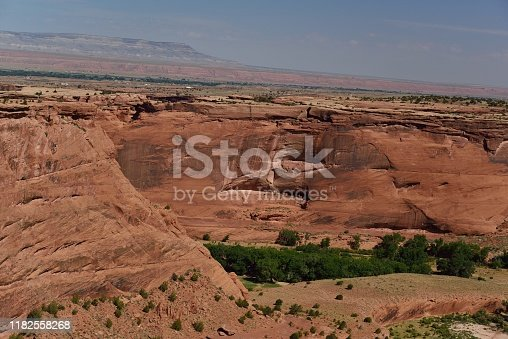 Looking on the far side of Canyon de Chelly, cliff dwellings of indigenous Americans from ancient times line the face of the canyon wall