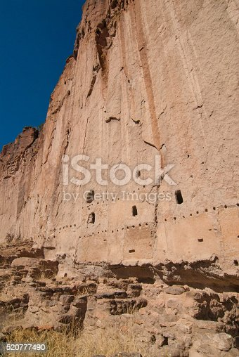 Multistory cliff dwellings at Bandelier National Monument in New Mexico with cave entrances, beam holes, and cavates carved into tuff.