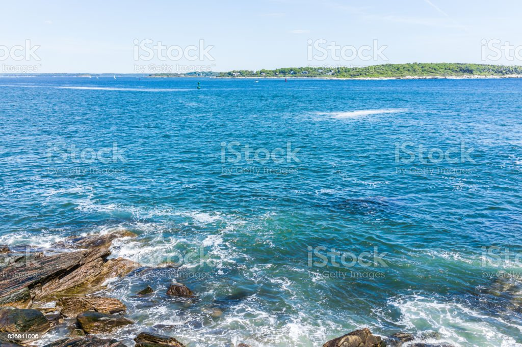 Cliff rocks aerial view by Portland Head Lighthouse in Fort Williams park in Cape Elizabeth, Maine during summer day overlooking Cushing Island stock photo