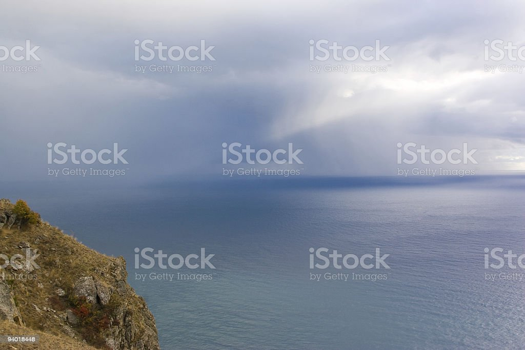 Cliff top and clouded sky over the ocean. stock photo