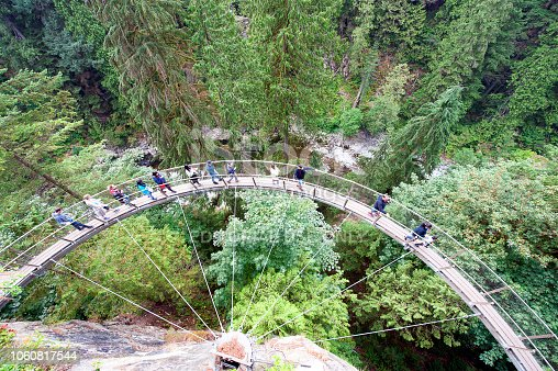 Capilano Park, Vancouver, B.C., Canada. People, mainly tourists, brave the expanse of the ravine overhang by walking around the narrow pedestrian arc of the midair cliff walk bridge over Capilano River coniferous woodland chasm, Vancouver, B.C., Canada