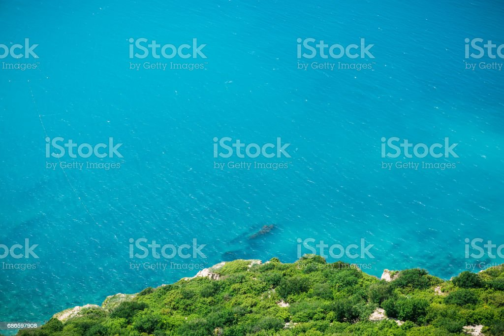 Cliff with frees and blue sea. Summer day on ocean royalty-free stock photo
