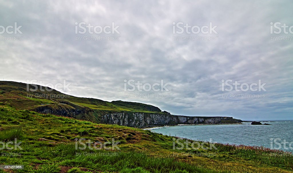 Cliffs along Irish Coast next to Carrick-a-rede under overcast skies stock photo