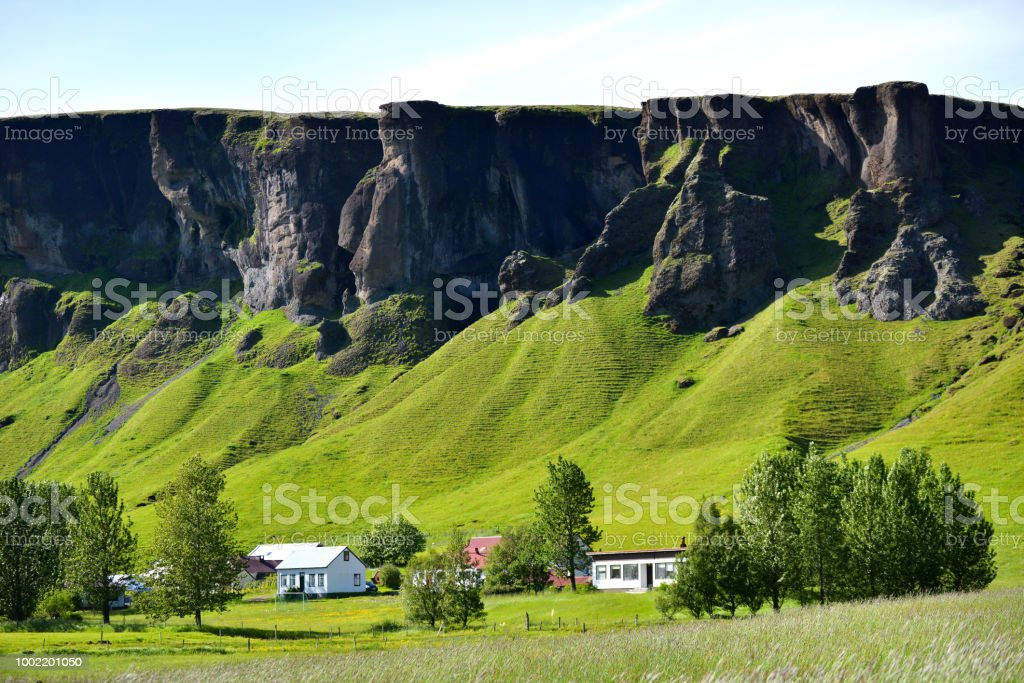 Cliffs and mountains with houses in the foreground in Iceland stock photo