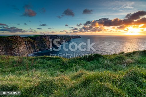 Overlooking ocean on a cliff with grass in foreground.