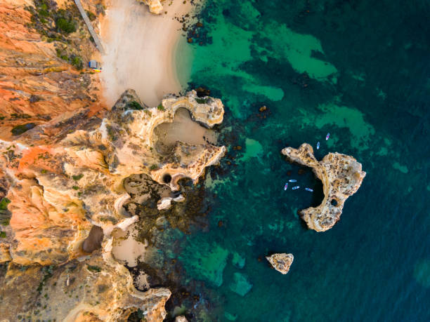 Cliffs with rock formations at Ponta da Piedade Rock formations at beach along coastline of Ponta da Piedade rocky coastline stock pictures, royalty-free photos & images