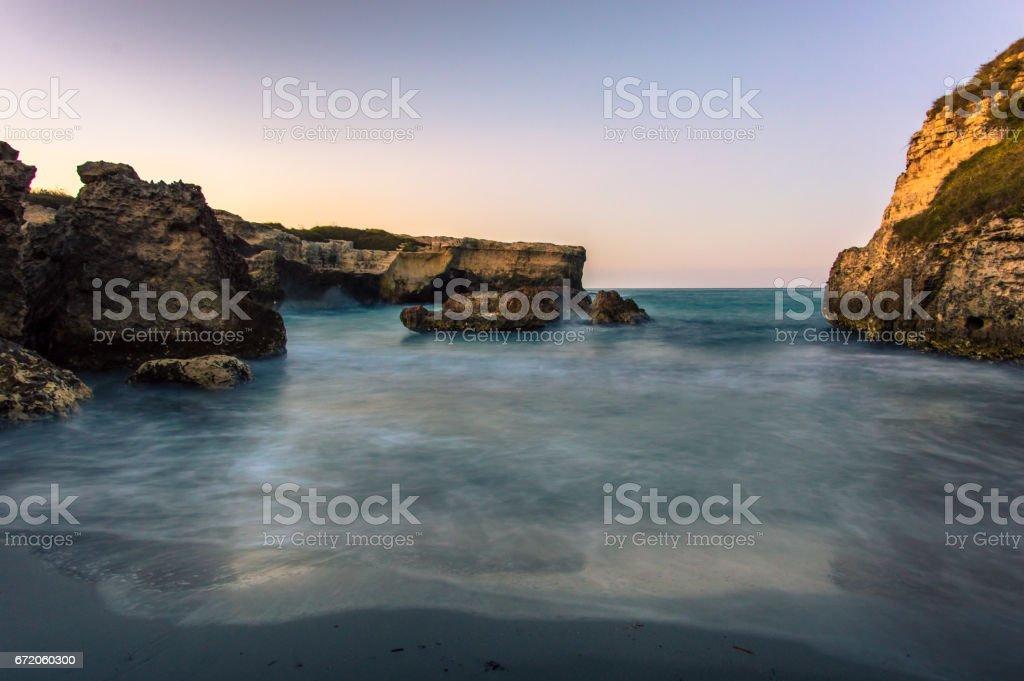 Cliffside view of horizon over water in Salento