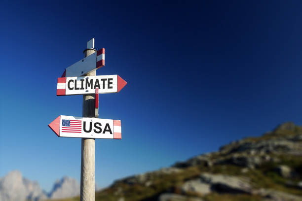 Climate change and American flag in two directions on road sign. Withdrawal of climatic agreement. stock photo