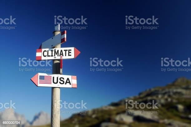 気候変動と道路標識には 2 方向でアメリカの国旗気候協定の撤退 - アメリカ合衆国のストックフォトや画像を多数ご用意