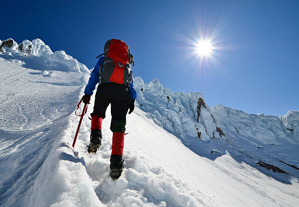 Climb higher A woman ascends ascends the ice-clad slopes of Mt. Hood under a brilliant sun (real sun-star). steep stock pictures, royalty-free photos & images