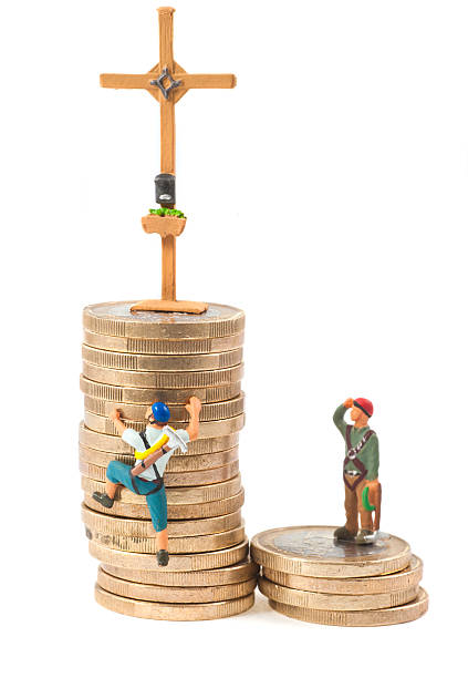 climb on tower of money - gipfelkreuz - figurine stock photos and pictures