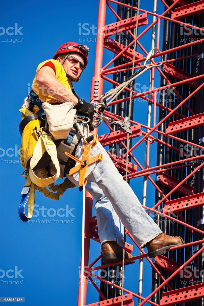 Climber ascending cell tower stock photo