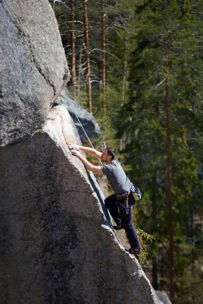 escalador sube a una roca empinada en el fondo del bosque. día de verano. marco vertical - foto de stock