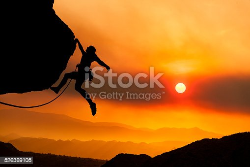Climber gripping the edge of a cliff.