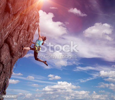 Elegant female athlete hanging at top of dangerous peak equipped with gear rope harness blue sky and terrific clouds on background and sunbeams shining from above