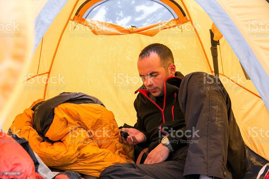 Climber inside Camping Tent Using Gadget stock photo