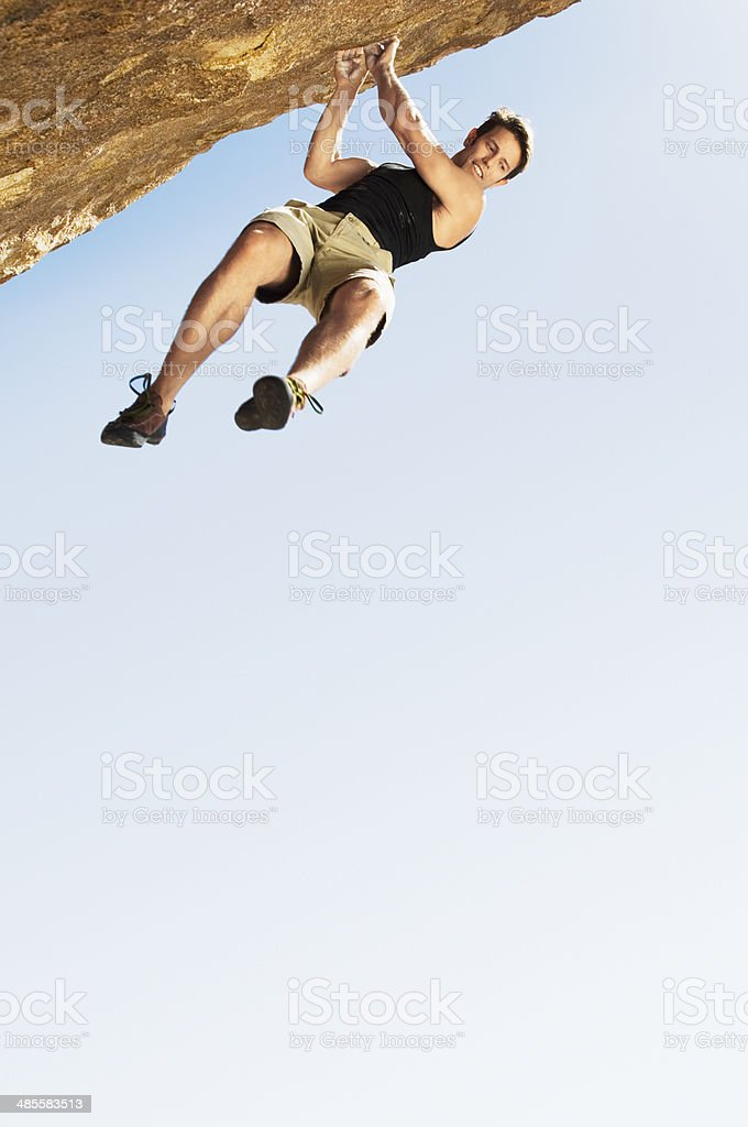 Climber Jumping off Cliff stock photo