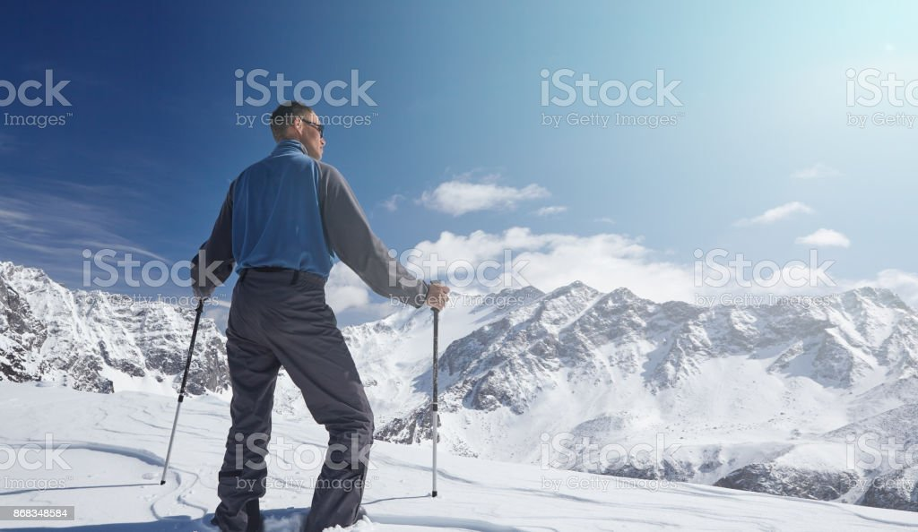 Climber looking at a snowy mountain landscape in a sunny winter day. stock photo