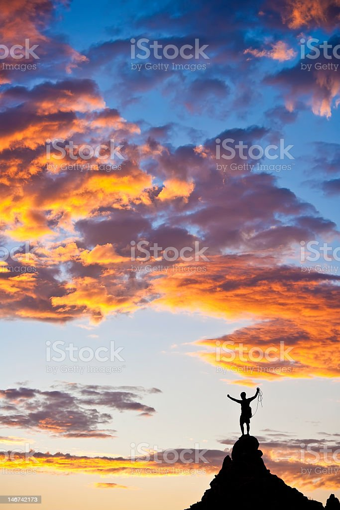 Climber on the peak of a climb with dramatic sky behind royalty-free stock photo