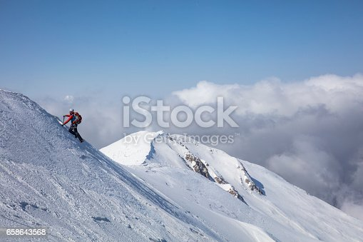 istock climber on the top of a mountain in winter 658643568