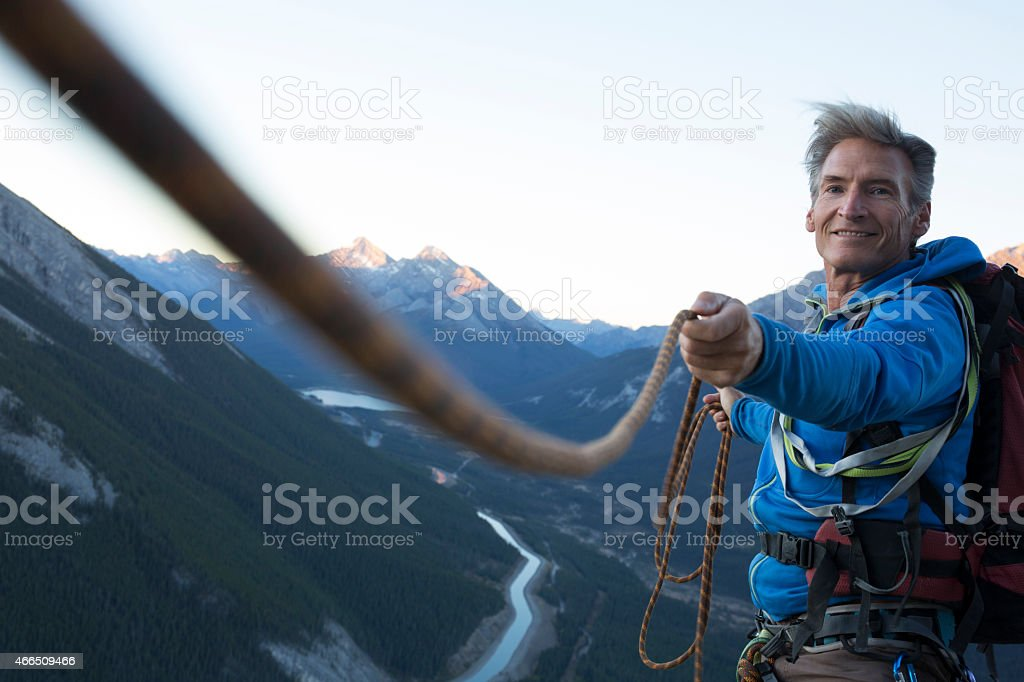 Climber pulls rope tight for teammate stock photo