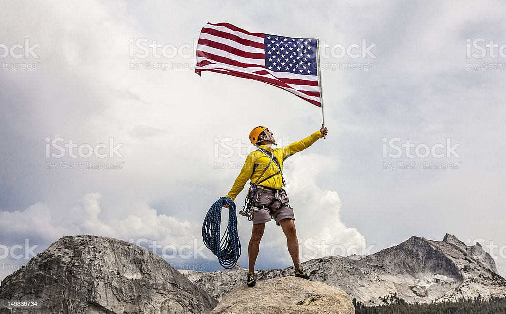 Climber raising an american flag on the summit. stock photo