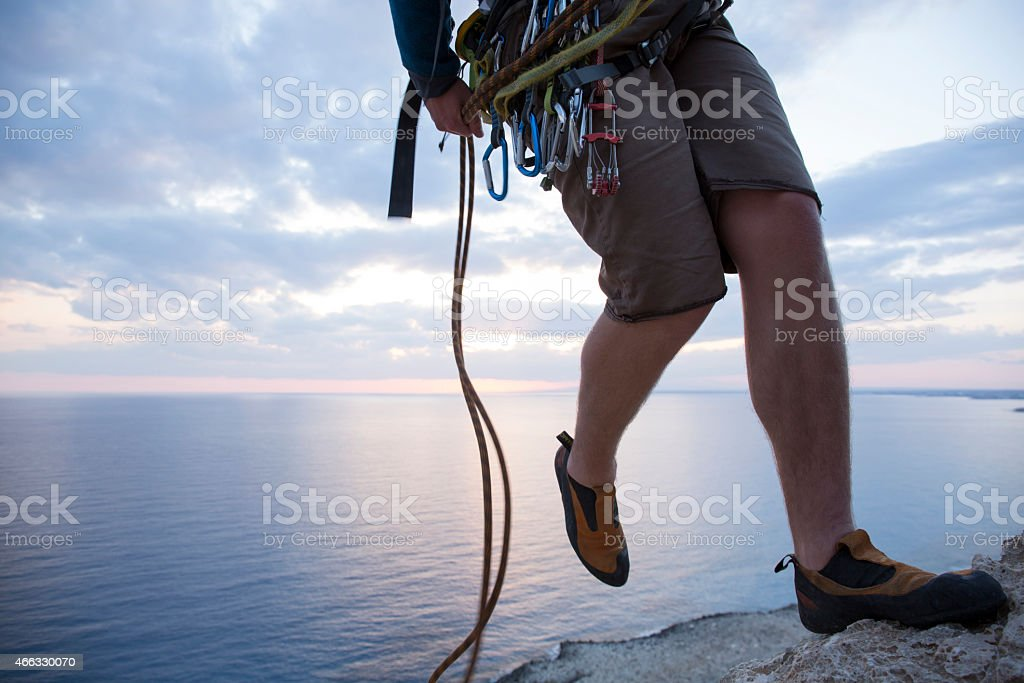 Climber rappels (abseils) from top of cliff stock photo