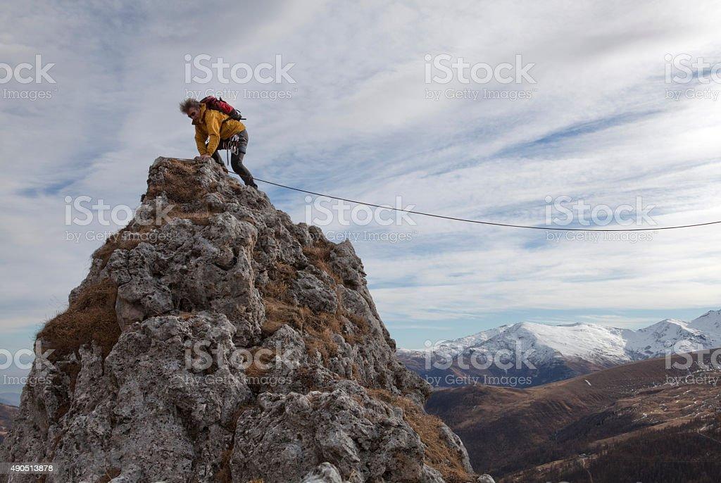 Climber reaches mountain summit stock photo