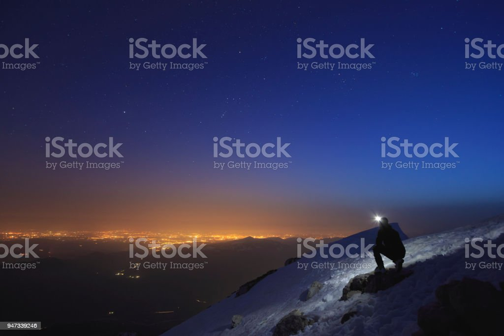 Climber shining a flashlight into the sky on top of a mountain stock photo