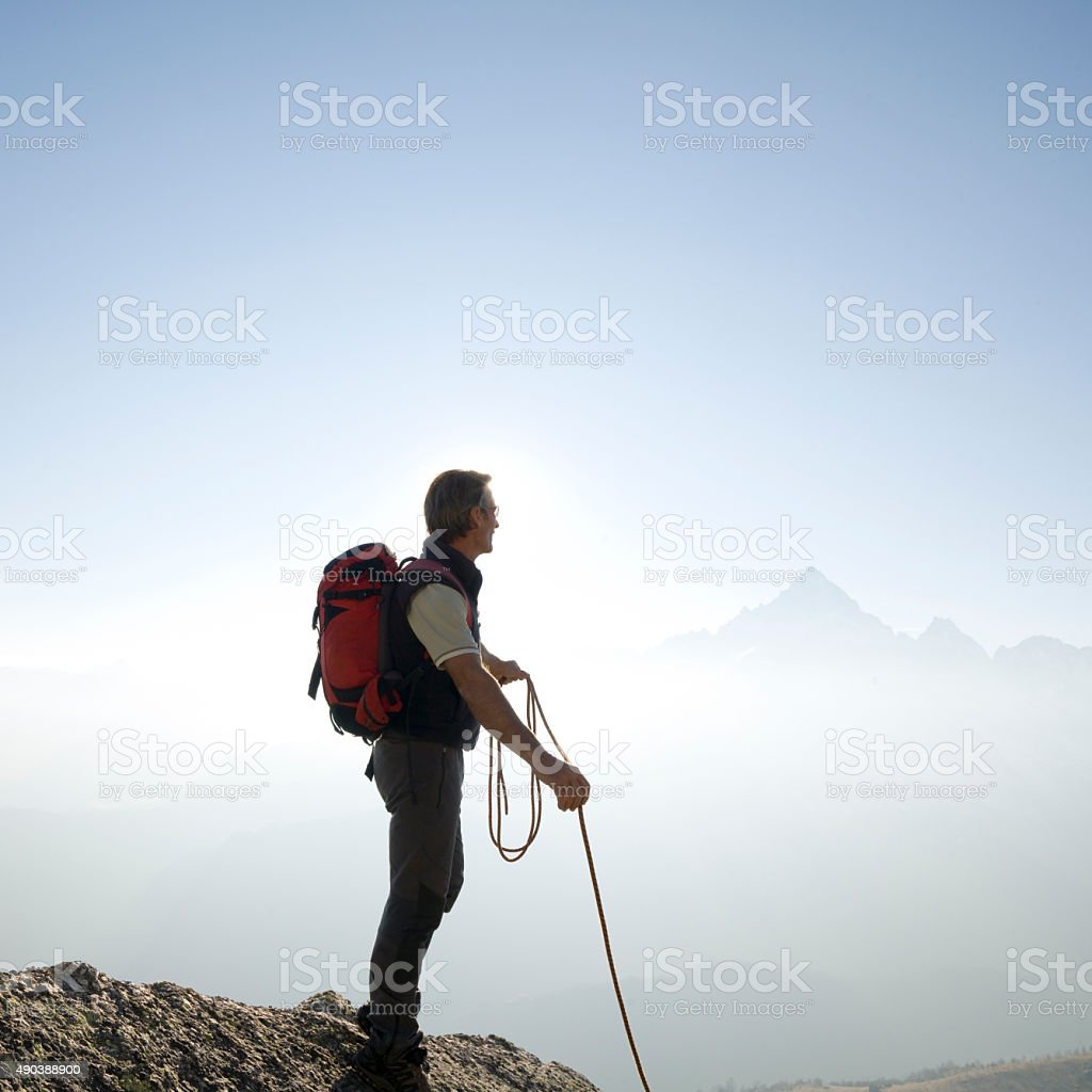 Climber stands holding rope on mountain summit stock photo