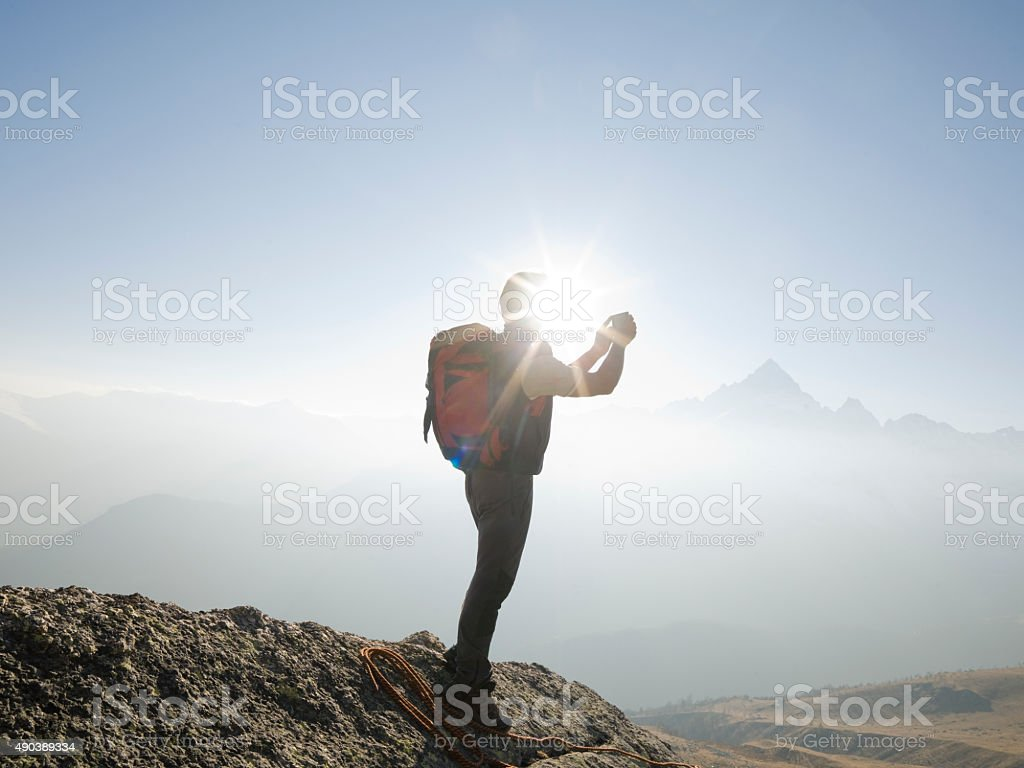 Climber stands taking picture on mountain summit stock photo