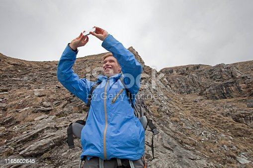 He has just finished climbing and is sending a photo with his phone