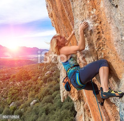 Female Climber Trying to keep Hold in last Effort to avoid deep fall down High rocky Wall in orange and blue Colours Forest Mountains and Sky on Background