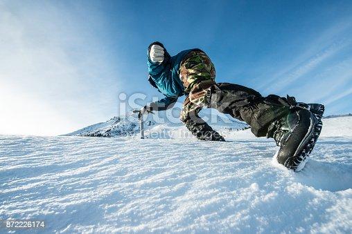 istock climber with an ice ax climb on the snowy mountain 872226174