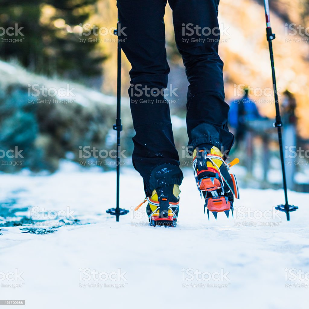 Climber with crampons on iced paths royalty-free stock photo