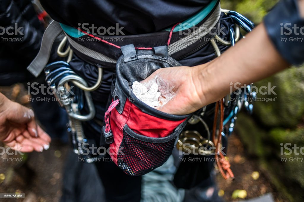 Climber woman coating her hands in powder chalk magnesium stock photo