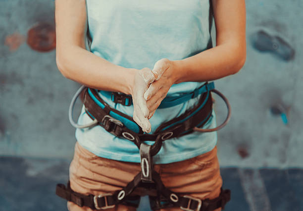 Climber woman coating her hands in powder Climber woman coating her hands in powder chalk magnesium and preparing to climb indoor, close-up safety harness stock pictures, royalty-free photos & images