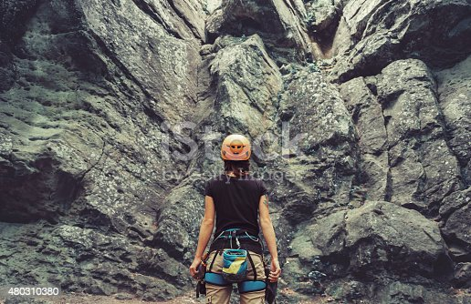 Young woman wearing in climbing equipment standing in front of a stone rock outdoor and preparing to climb, rear view