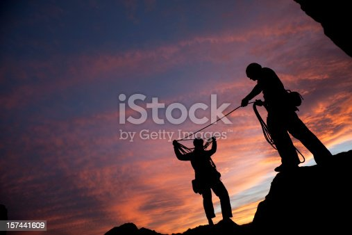 Two mountain climbers coil their rope after a climb at dusk
