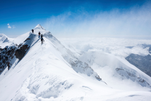 Climbers balancing in blizzard on a narrow ridge of Lyskamm (aka Maneater, 4480 m, Alps)