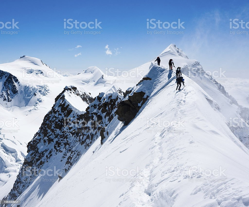 Climbers balancing in blizzard stock photo
