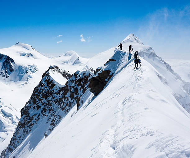 climbers balancing in blizzard - snowy mountains stock photos and pictures