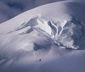 Italy. Piedmont. Monte Rosa Region. A climbing couple on a glacier  with huge crevasses below the Monte Rosa.