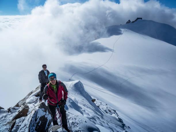 bergsteiger-paar auf einem verschneiten bergrücken. - gute winterjacken stock-fotos und bilder