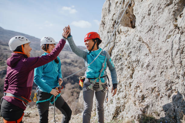 climbers giving high fives after successfully finishing climb - all vocabulary foto e immagini stock