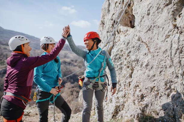 climbers giving high fives after successfully finishing climb - all vocabulary zdjęcia i obrazy z banku zdjęć